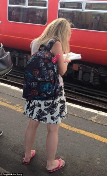 An unknown commuter was pictured at Clapham Junction station in London on Thursday evening with a long pink object sticking out of her holdall